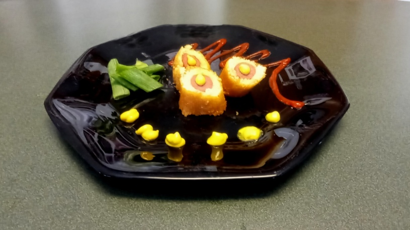 Corn dog with tomato, vinegar, and corn syrup reduction, our signature mustard sauce, and salade de tondeuse à gazon